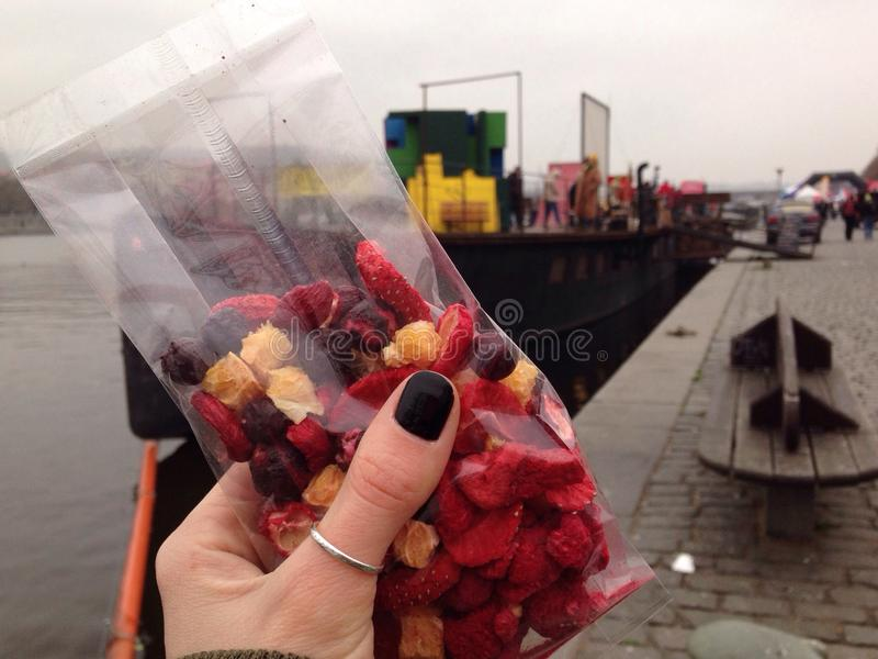 hand holding dried fruits on a background of the river and the ships royalty free stock images