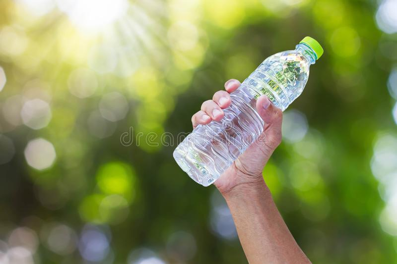 Hand holding drinking water bottle on blurred green bokeh background. Healthy drink concept stock image