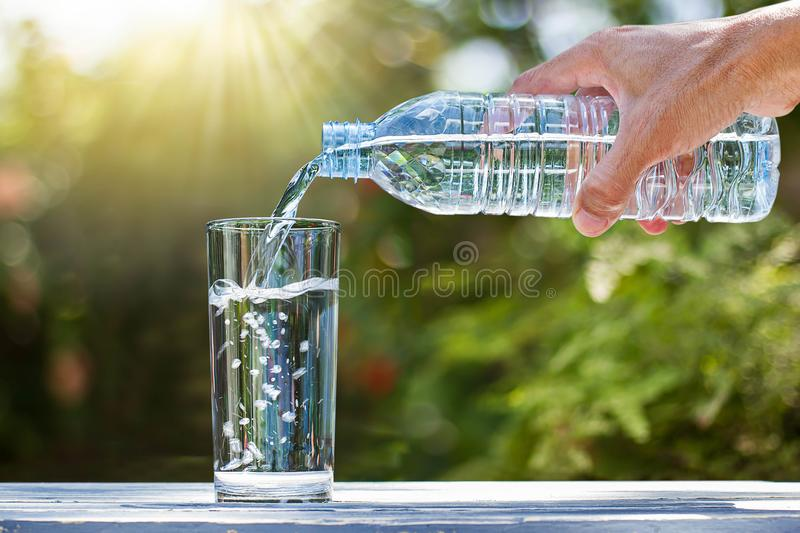 Hand holding drinking water bottle pouring water into glass on wooden table. On blurred green nature background stock photo