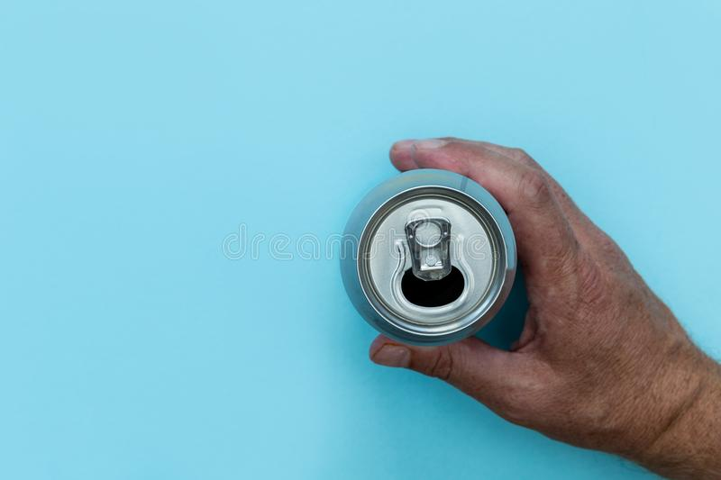 Hand holding drinks can on blue background royalty free stock image