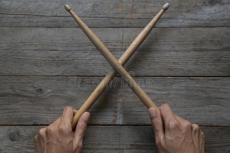 Hand holding drum stick on black table background. Music practice concept stock photos