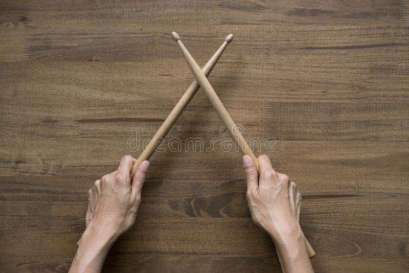 Hand holding drum stick on black table background. Music practice concept stock image