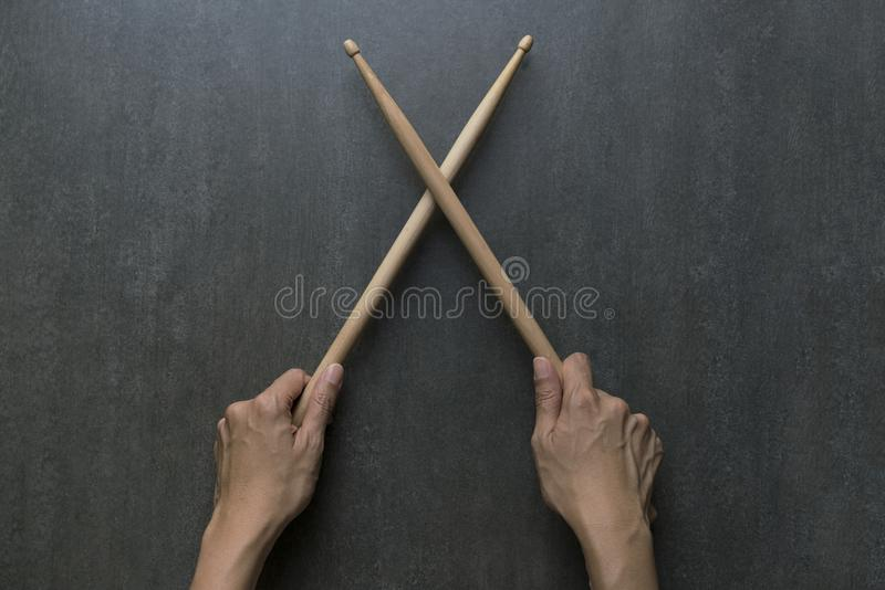 Hand holding drum stick on black table background. Music practice concept royalty free stock images