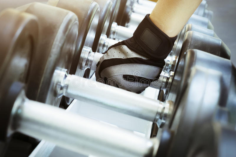 Hand holding the dumbells in the gym.  royalty free stock image