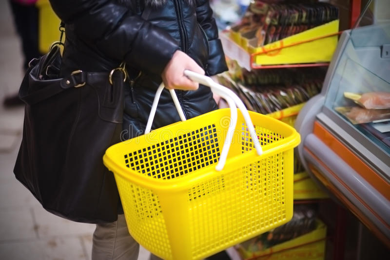 Hand holding empty shopping basket. Photo of Hand holding empty shopping basket stock photo