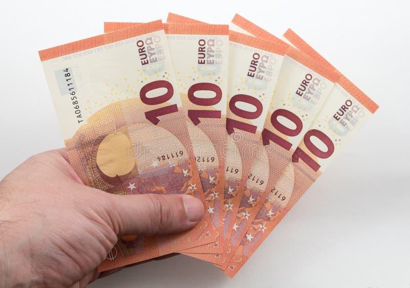 Hand holding 10 Euro notes. A Hand holding 10 Euro notes in a fan shape royalty free stock photo