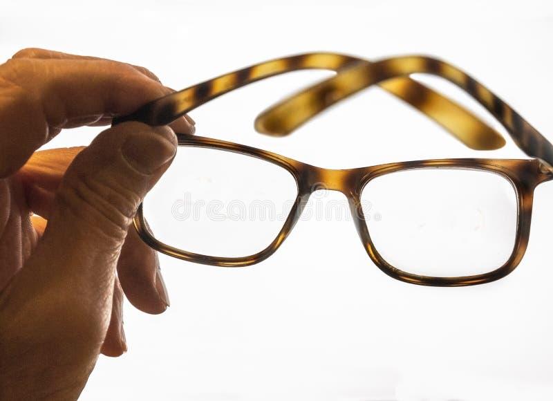 Hand holding eyeglassen stock afbeelding