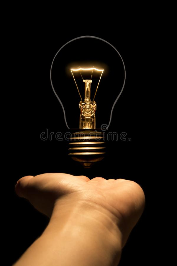 Hand holding a filament lamp on a black background royalty free stock images
