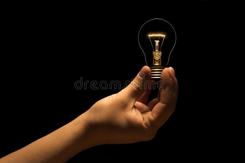 Hand holding a filament lamp on a black background royalty free stock photos