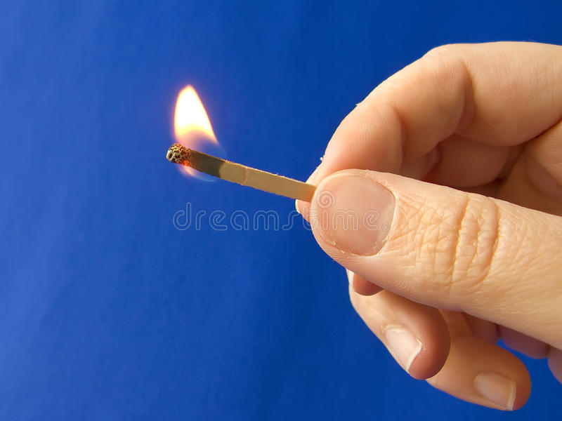 A hand holding a fired matchstick royalty free stock photography