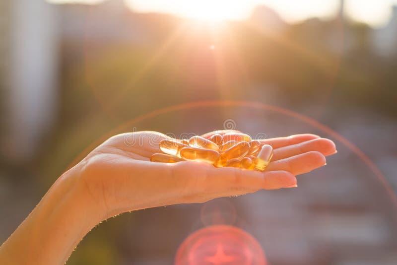 Hand holding fish oil Omega-3 capsules, urban sunset background. stock images