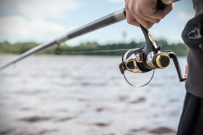 Hand holding a fishing rod with reel. Focus on Fishing Reels stock photography