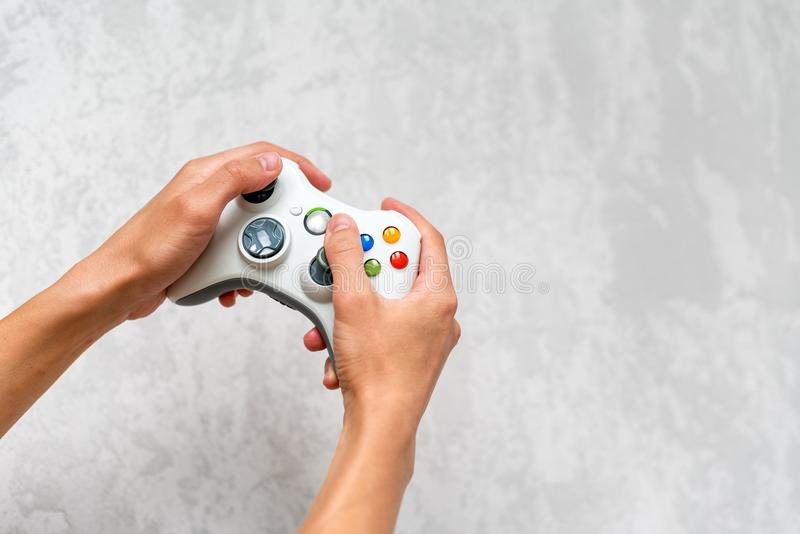 Hand holding gamepad on grey concrete background. Man with controller playing video game at home. Leisure and entertainment. Video royalty free stock images