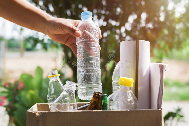 Hand holding garbage bottle plastic putting into recycle bag. For cleaning royalty free stock images