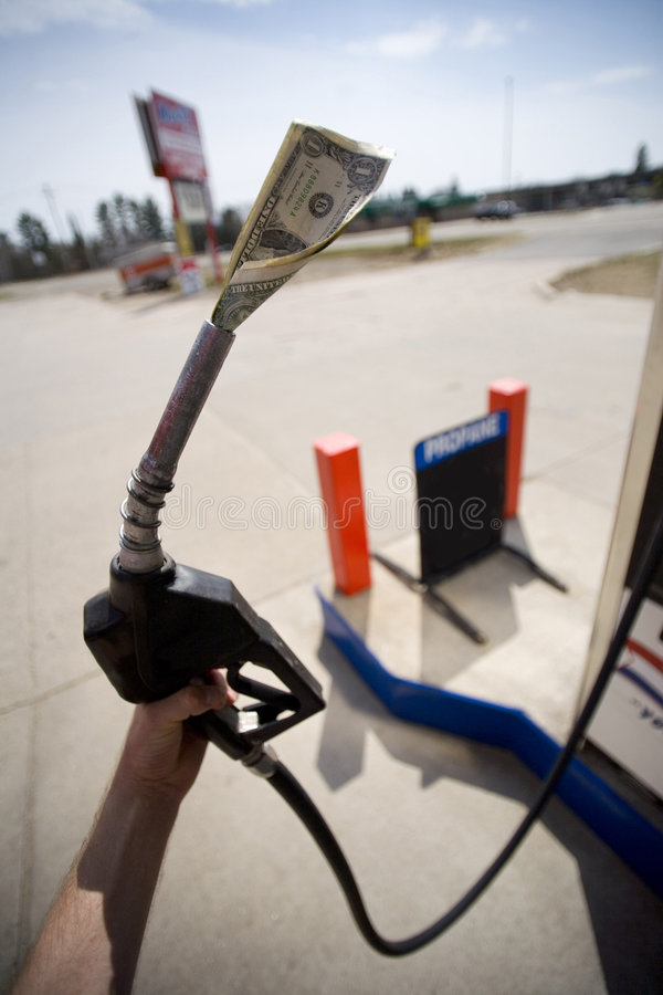 Hand holding gas pump with money in nozzle royalty free stock image