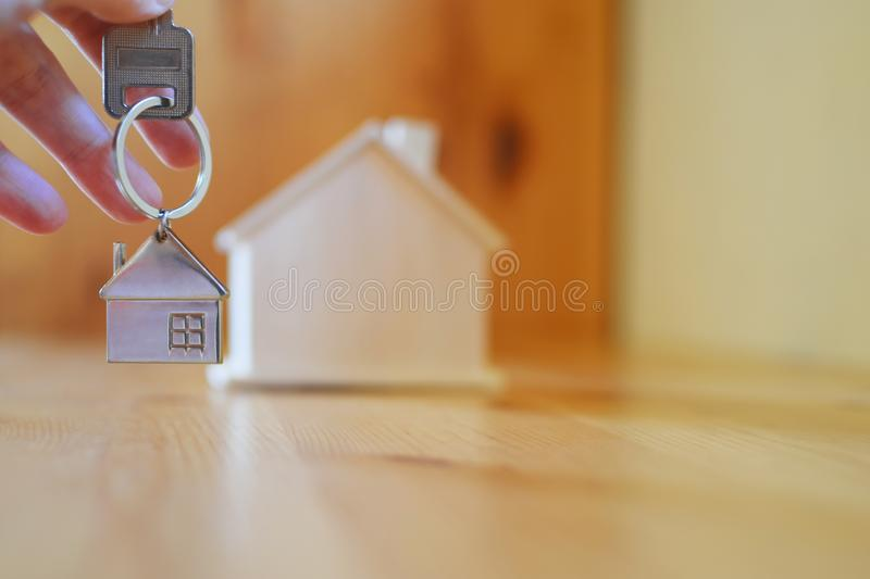 Hand holding giving key chain with house shaped pendant. On blurred wooden table and home model background with copy space. Real estate, buying moving new home royalty free stock images
