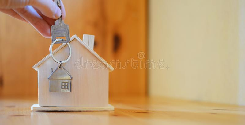 Hand holding giving key chain with house shaped pendant. On blurred wooden table and home model background with copy space. Real estate, buying moving new home stock photos
