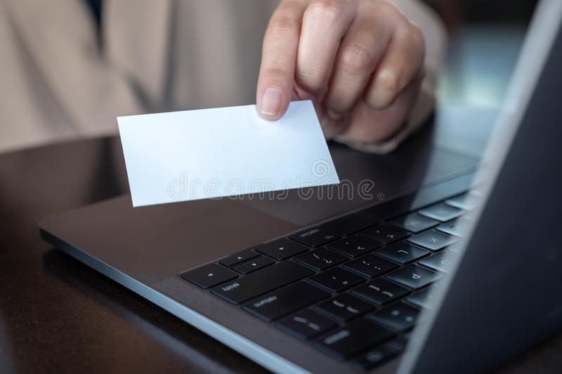 Hand holding and giving white empty business card with laptop on wooden table in office. A hand holding and giving white empty business card with laptop on royalty free stock images