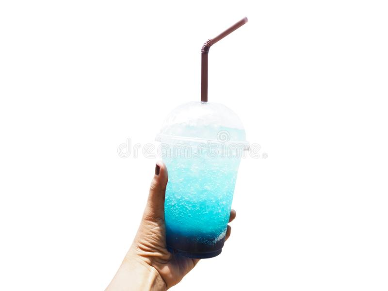 Hand holding glass of Blue Hawaii drink with ice over summer beach background royalty free stock images