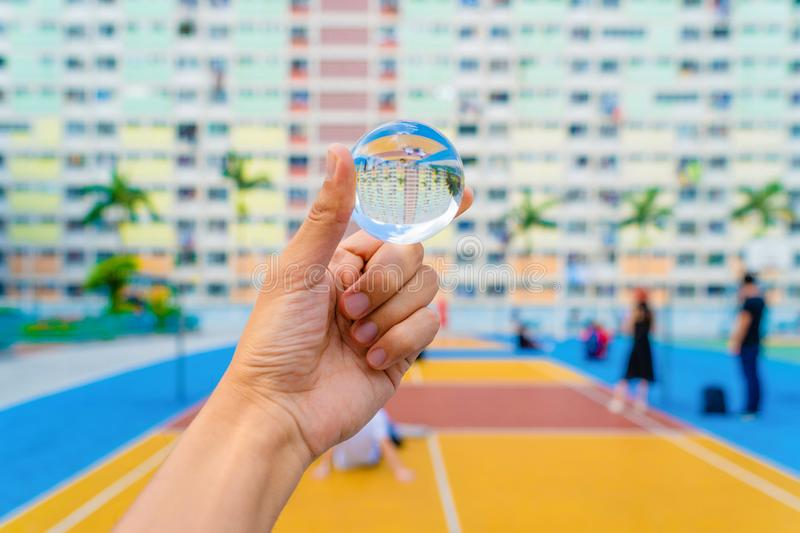 Hand holding a glass or crystal ball at colorful rainbow pastel building with basketball court and facade windows in public park royalty free stock photo