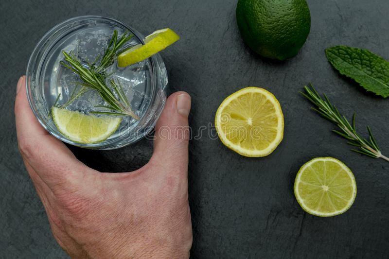 Hand holding glass of gin tonic with ice and lime dark background stock image