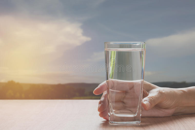 Hand holding a glass of pure water. Hand holding a glass royalty free stock photos
