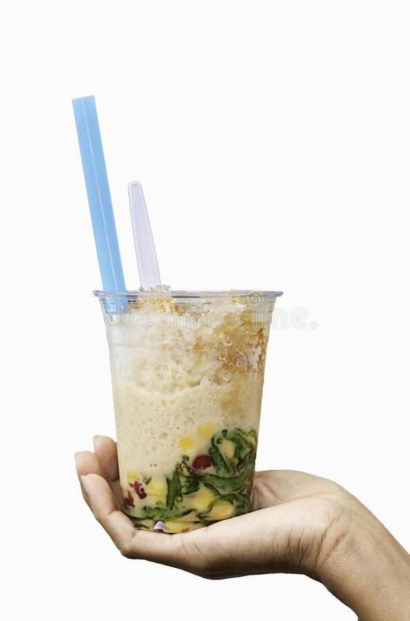 Hand holding a glass of sweet candy Thailand. With ice and coconut milk on a white background with clipping path royalty free stock image