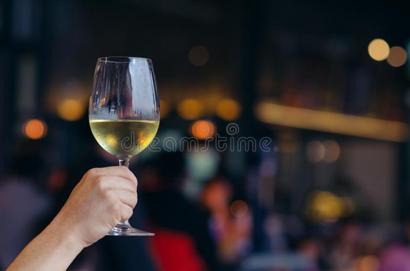 Hand holding a glass of white wine with colorful bokeh light in restaurant royalty free stock photography