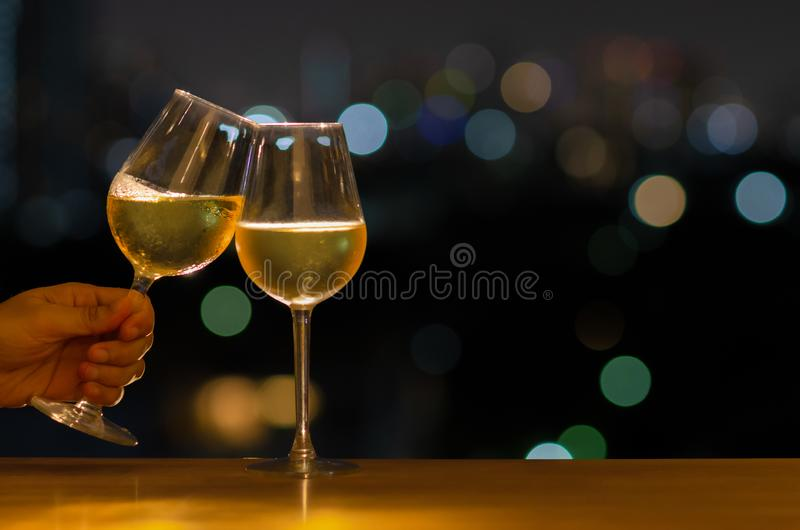 Hand holding a glass of white wine toasting to celebration and party concept put on wooden table of rooftop bar with colorful stock image