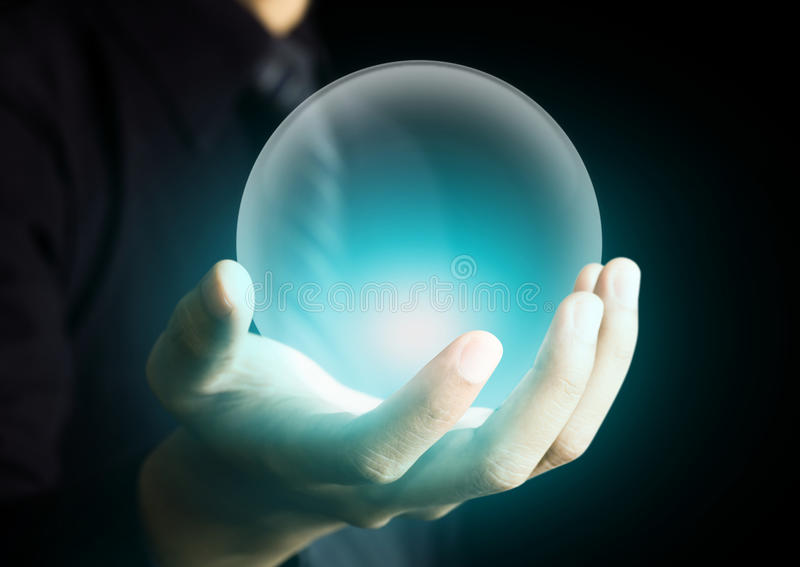 Hand holding a glowing crystal ball. Hand holding glowing crystal ball