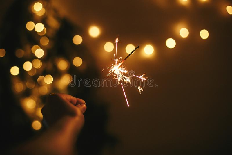 Hand holding glowing sparkler on background of golden christmas lights, celebrating in dark festive room. Space for text. Happy. New Year eve party. Happy royalty free stock photography