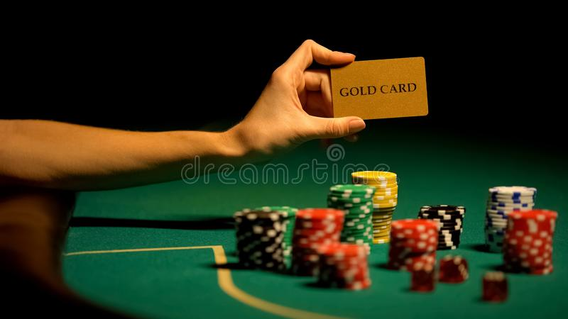 Hand holding gold card, gambling chips on table, illegal casino for VIP-clients. Stock photo stock image