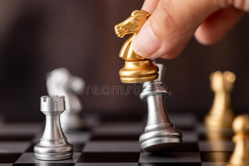 Hand holding gold horse attack silver king in game. On the chessboard with wooden background, battle, bishop, business, castle, challenge, checkmate, choose stock photo