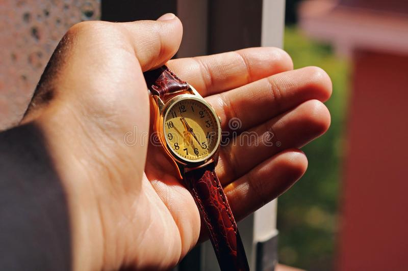Hand holding a gold watch. stock photography