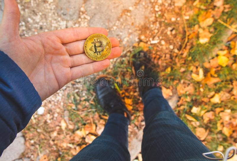 Hand holding a golden bitcoin , blurred background of legs and body . View from above, top-view. Concept of  exchange value, money royalty free stock images