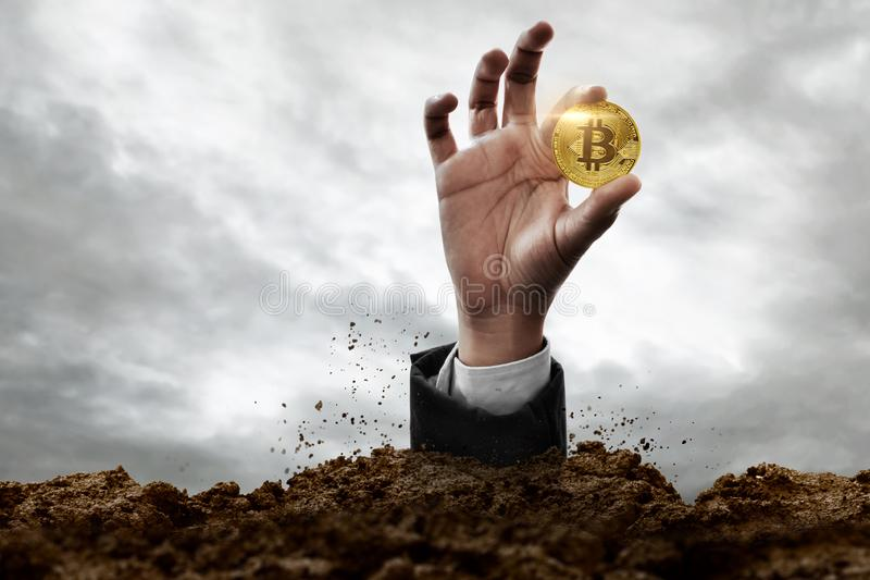 Hand holding golden bitcoin from the ground. Hand hold golden bitcoin from the ground royalty free stock photos