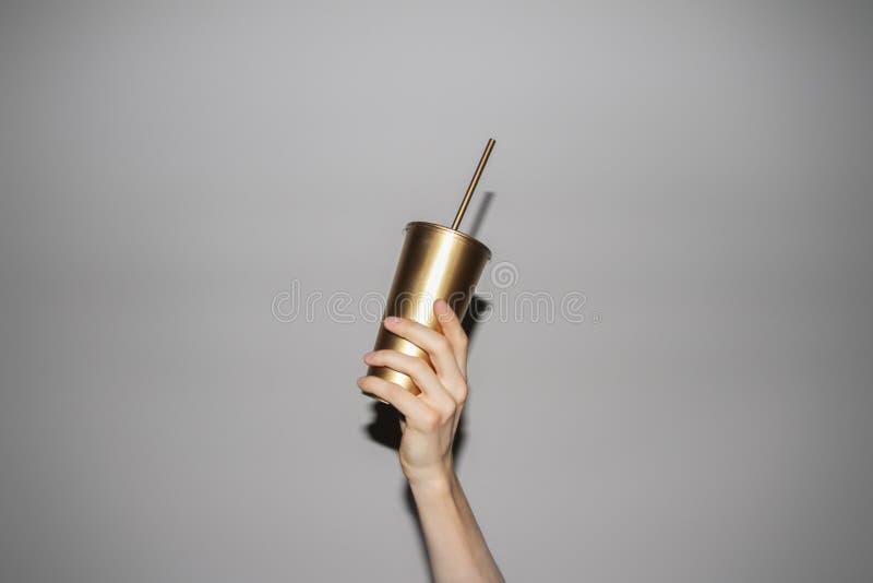 Hand Holding Golden Soda Cup. Conceptual photo of hand holding golden soda cup with straw stock photos