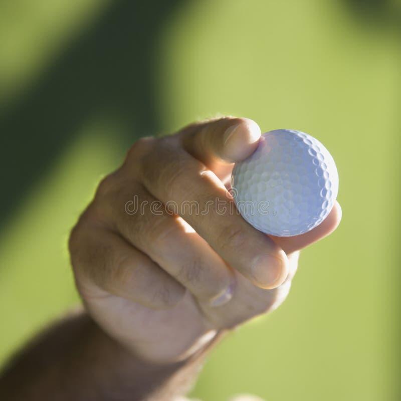 Hand holding golf ball. royalty free stock photos