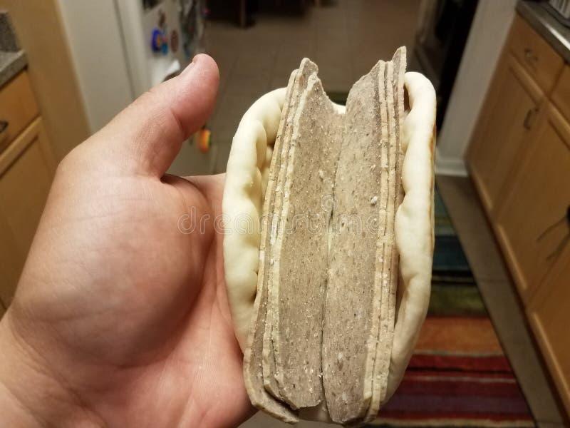 Hand holding Greek lamb meat sandwich in kitchen stock photo