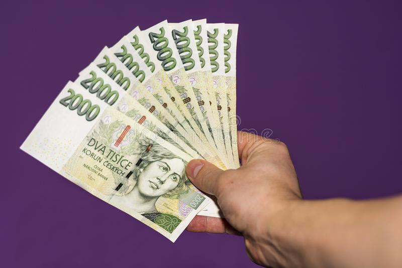Hand holding green Czech banknotes stock images