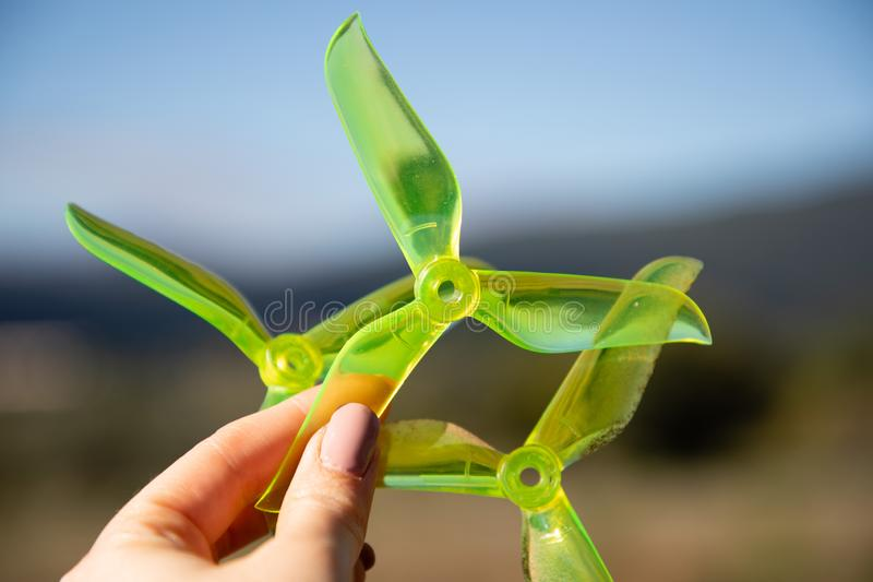 Hand holding green racing drone propellers. With copy space royalty free stock photo