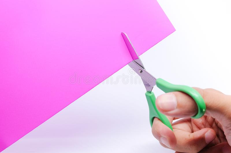 Hand holding green scissors used for cutting violet paper , isolated on white background. stock image