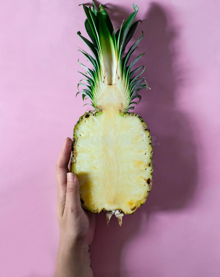 Hand is holding half of fresh pineapple on pink background stock photos