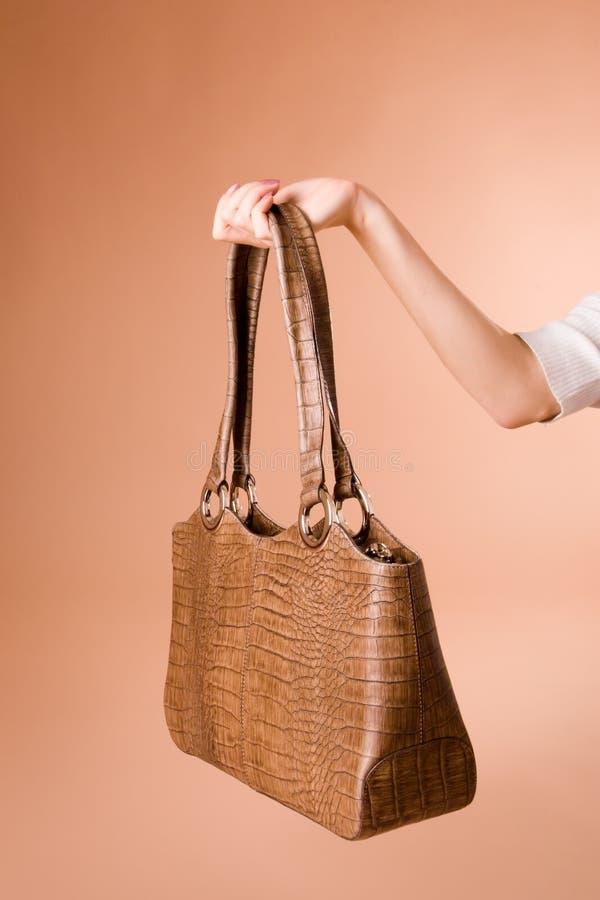 Hand holding handbag on the beige background