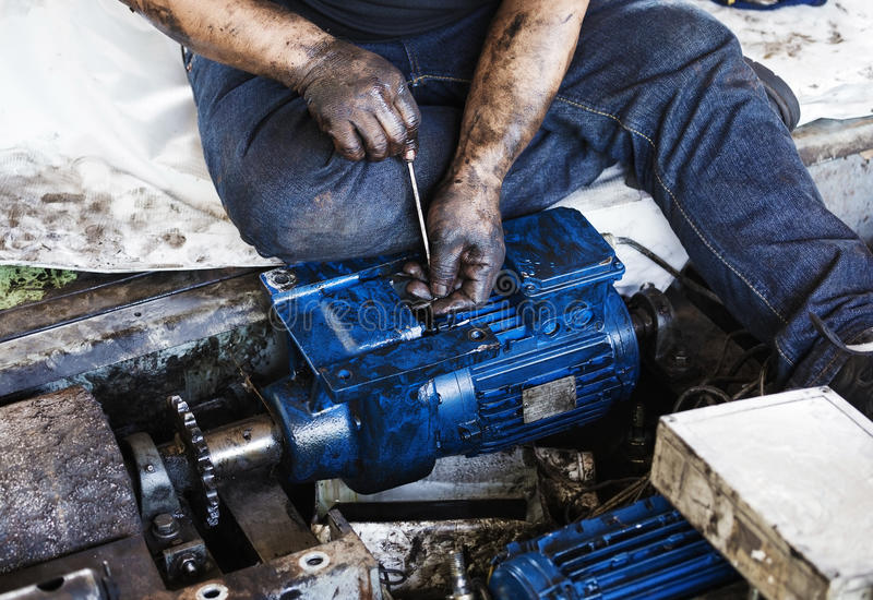 Hand holding hexagonal wrench and during maintenance work of electric motor royalty free stock image