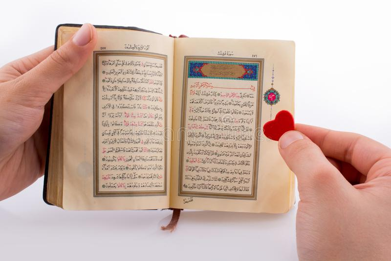 The Holy Quran. Hand holding The Holy Quran with a heart on a white background royalty free stock image