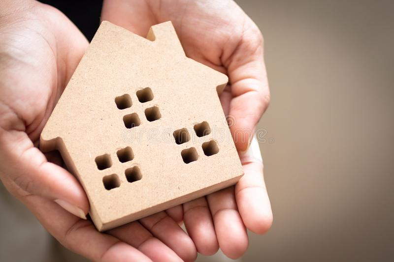 Hand holding home model, happy homes for families.  stock photo