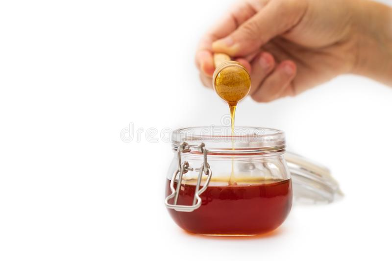 Hand holding a honey dripper on white background. Food concept stock images
