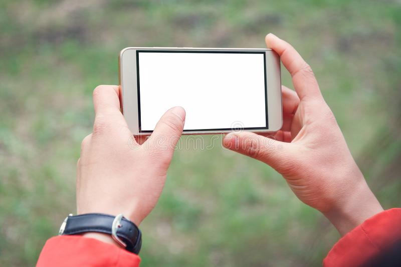 Hand is holding horizontal smartphone for show and touch with white screen is outdoor stock photo