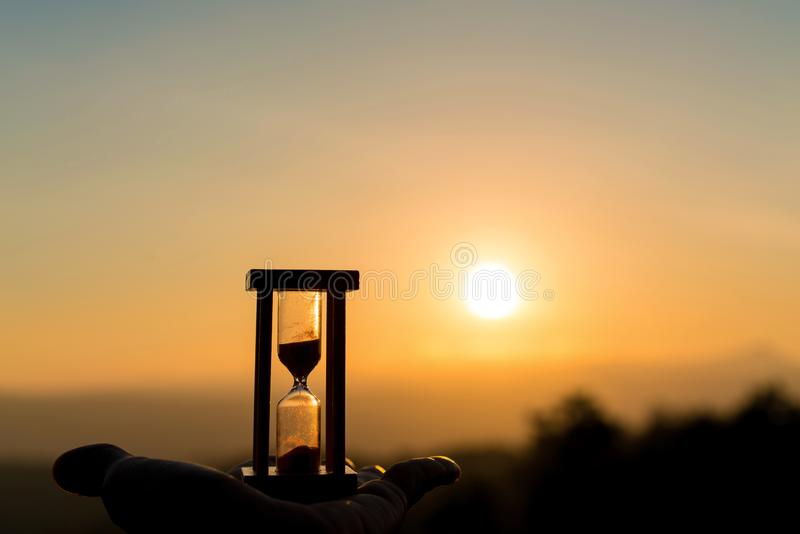 Hand holding Hourglass with sunrise in the morning, Time Concept.  stock photo